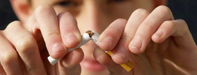 Une personne arrête de fumer par l'hypnose et coupe une cigarette en 2 avec ses doigts